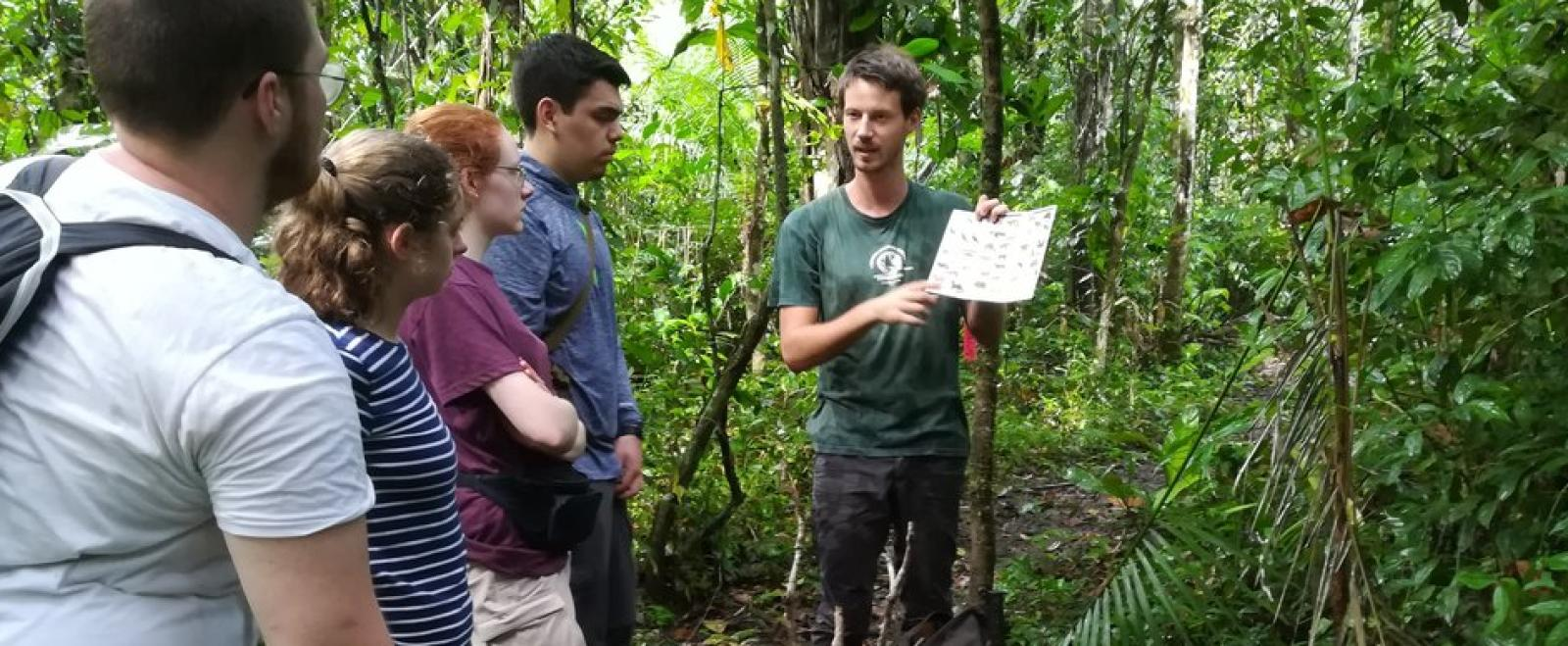 A group of Conservation volunteers in the Amazon Rainforest listen to a briefing from a staff member.